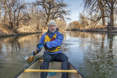 cache la poudre: senior canoe paddler in a canoe