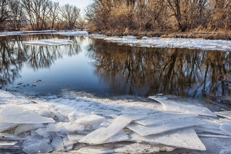 cache la poudre: spring scenery with icy shores Stock Photo