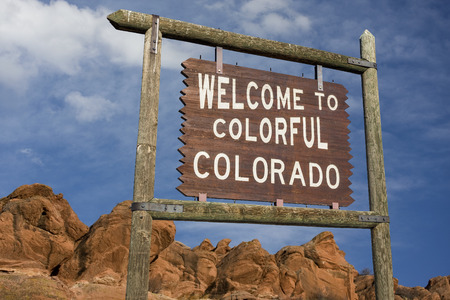 welcome sign: welcome to colorful Colorado roadside wooden sign with red sandstone cliff in background Stock Photo