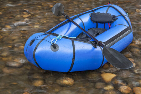 a blue pacraft (one-person light raft used for expedition or adventure racing) with a kayak paddle against a shallow river