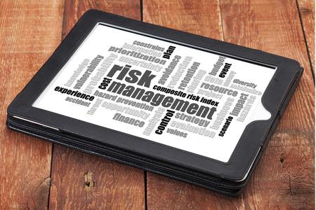 risicobeheer word cloud - een digitale tablet op een rustieke houten tafel