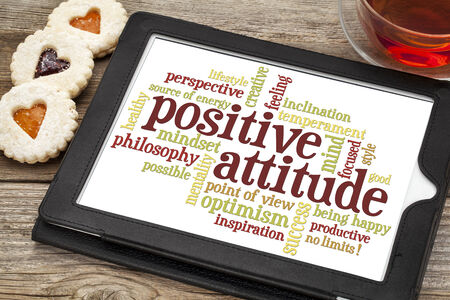 positive attitude word cloud on a digital tablet with a cup of tea and heart cookies Banco de Imagens