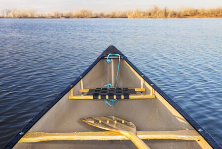 canoe bow with a wooden paddle on a calm lake, Fort Collins, Colorado
