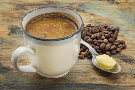 coffee spoon: a cup of fresh fatty coffee with butter and coconut oil - ketogenic diet concept Stock Photo