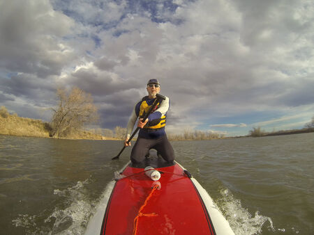 paddler: mature male paddler in wetsuit and life jacket enjoying workout on a stand up paddle board (SUP) Stock Photo