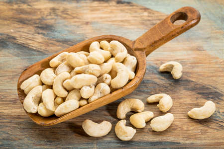 cashew nuts on a rustic wooden scoop against grunge painted wood background