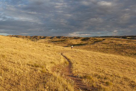 soapstone: sunrise over Colorado prairie with a distant mountain biking figure - Soapstone Prairie Natural Area, Fort Collins