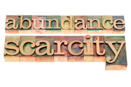 scarcity: abundance and scarcity - isolated words in n letterpress wood type blocks stained by color inks Stock Photo