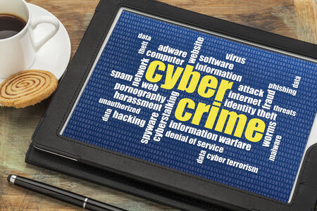 internet concept - cybercrime word cloud on a digital tablet photo