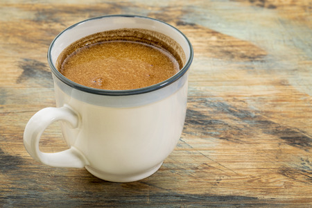 a cup of fresh fatty coffee with butter and coconut oil - ketogenic diet concept Stock Photo