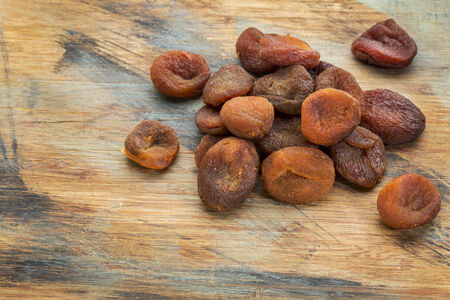 a pile of sun dried Turkish apricots on grunge painted wood surface