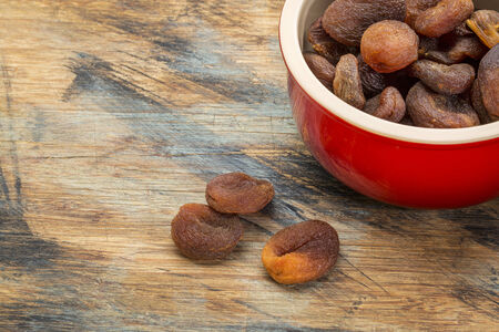 dried Turkish apricots in a stoneware bowl on a grunge painted wood surface Stok Fotoğraf
