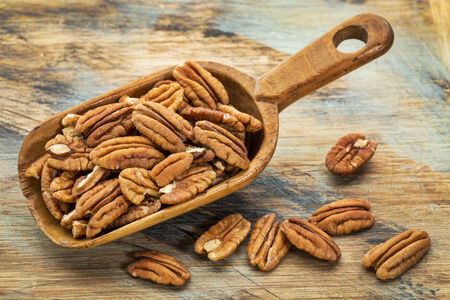 pecan: pecan nuts in a rustic scoop against a grunge wood background