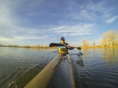 fort collins: senior male paddler enjoys workout in a racing kayak in sunset light on a calm lake in Colorado