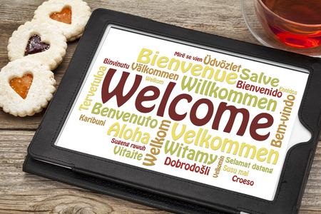 차와 심장 쿠키 한잔과 함께 디지털 태블릿에 다른 언어로 환영 단어 구름
