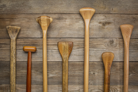 shafts: grips and shafts of old wooden canoe paddles against weathered wood background Stock Photo