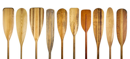 a row of 10 wooden canoe paddles, a variety of styles and shapes - paddling concept photo