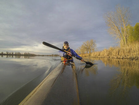 paddler: senior male paddler enjoys morning workout in a slim racing kayak on a calm lake in Colorado Stock Photo