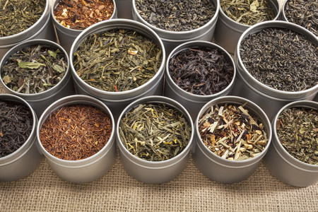 samples of loose leaf green, white, black red, and herbal tea in metal cans on canvas background photo