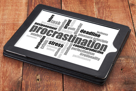 procrastination word cloud on a digital tablet against red barn wood Stock Photo