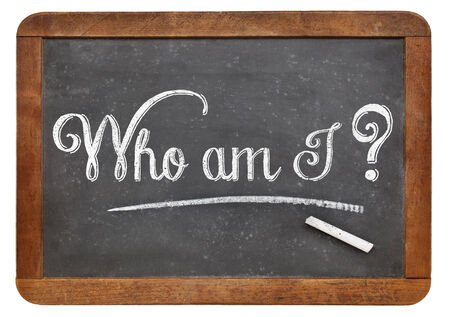 who: Who am I ? A philosophical question  on a vintage blackboard with white chalk, isolated on white Stock Photo