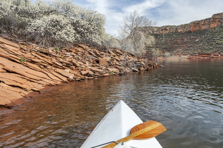 canoe paddle: springtime canoe paddling - canoe bow with a paddle on Horsetooth Reservoir near Fort Collins, Colorado in spring scenery