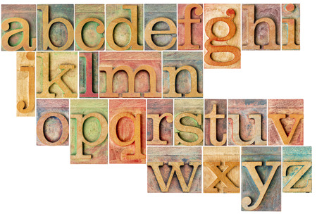 complete English lowercase alphabet - a collage of 26 isolated antique wood letterpress printing blocks, stained by color inks Stock Photo