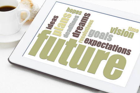 future, dreams, goals, and plans word clouf on a white digital tablet with a cup of coffee