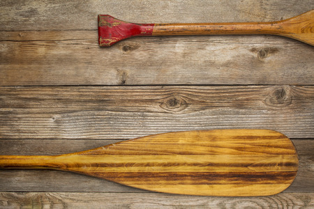canoe paddle: blade and grip of wooden canoe paddle against rustic wood background with a copy space