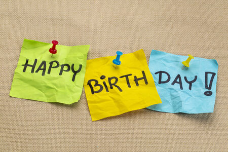 happy birthday greetings on sticky notes against burlap canvas