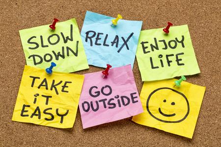 El retraso, relaja, tómalo con calma, disfrutar de la vida - recordatorios de estilo de vida de motivación en las notas adhesivas de colores Foto de archivo - 28078017