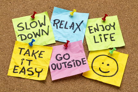 slow down, relax, take it easy, enjoy life -  motivational lifestyle reminders on colorful sticky notes Фото со стока