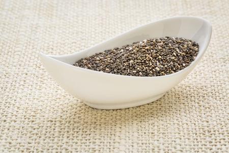 hispanica: chia seeds (Salvia Hispanica) in a small white bowl against burlap canvas
