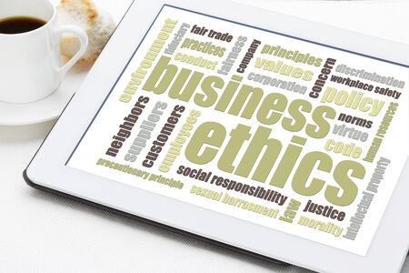 business ethics: business ethics word cloud on a digital tablet with a cup of coffee Stock Photo