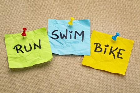 swimming race: run, bike, swim - triathlon or fitness concept - words on sticky notes