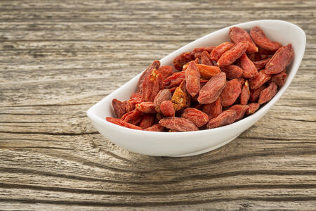 superfruit: dried goji berries in a small ceramic bowl against grained wood Stock Photo