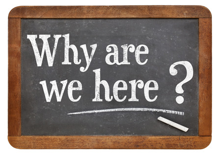here: Why are we here question  on a vintage blackboard isolated on white