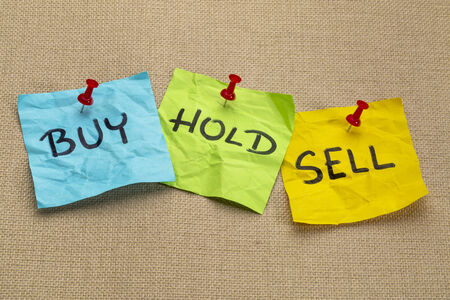 sell: buy, hold, sell - investing concept - handwritten words on sticky notes Stock Photo