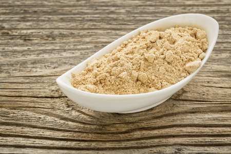 adaptogen: maca root powder in a small ceramic bowl against grained wood