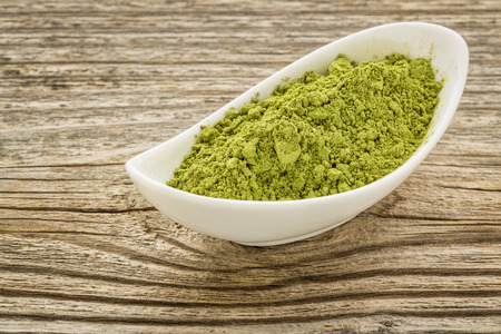 moringa leaf powder in a small ceramic bowl against grained wood photo