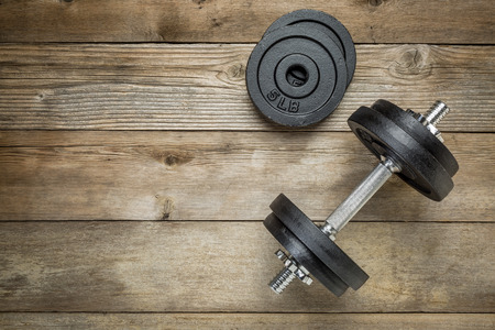 exercise weights - iron dumbbell with extra plates on a wooden deck Stok Fotoğraf