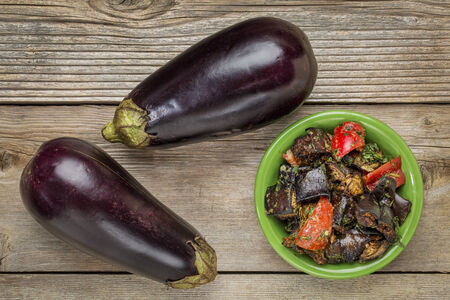 roasted spicy eggplant salad with bell pepper and two fresh fruits - top view on a rustic wood table