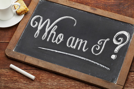 who: Who am I ? A philosophical question  on a vintage blackboard with white chalk with a cup of coffee