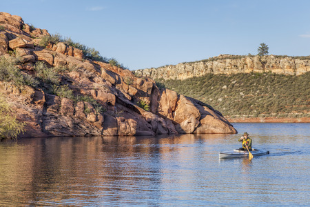 horsetooth reservoir: senior male paddling a decked expedition canoe on Horsetooth Reservoir near Fort Collins, Colorado