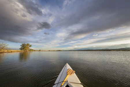loveland: canoe bow with a paddle on a lake - wide angle fisheye perspective - Lonetree Reservoir near Loveland, Colorado