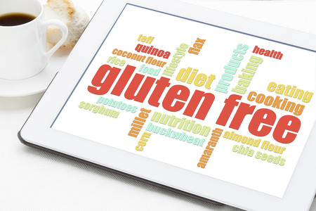 celiac disease: gluten free cooking word cloud on a digital tablet with a cup of coffee Stock Photo