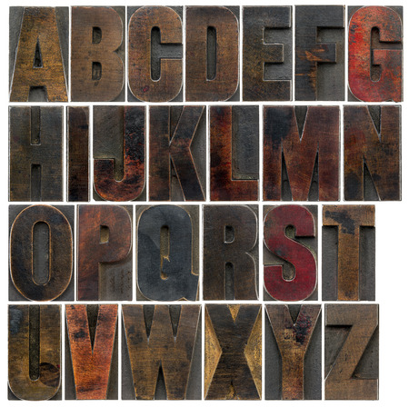 a complete English uppercase alphabet - a collage of 26 isolated antique wood letterpress printing blocks, stained by dark color inks photo