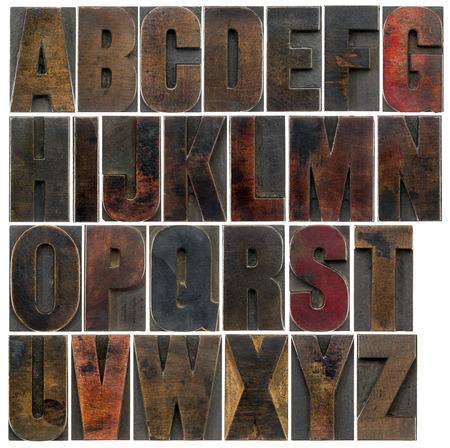 tipos de letras: un completo Inglés alfabeto mayúscula - un collage de 26 aislados antiguos bloques de impresión de tipografía de madera, manchado por las tintas de color oscuro Foto de archivo