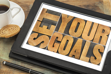 set your goals  - word abstract in vintage letterpress wood type on a digital tablet Stock Photo