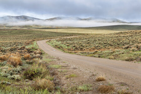 sagebrush: dirt road in a mountain valley with hills covered by sagebrush in early spring morning Stock Photo